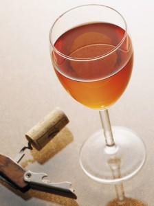Glass of rose wine beside a corkscrew with a cork