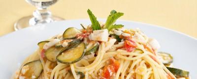 ricetta Spaghetti con sugo di branzino, accompagnati da zucchine e foglioline di menta fresca.
