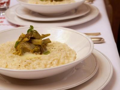Risotto ai carciofi con accompagnamento di fonduta di fontina e latte e guarnito con foglie di maggiorana.