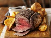 Sliced roast beef on a wooden board with roast potatoes