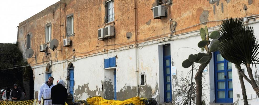 Tonnarotti e rais (rispettivamente ciurma e capo della tonnara) preparano le reti, davanti all'edificio che fa da quartier generale dei pescatori (Foto di Studio Spagoni+Mulas)