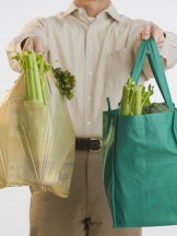 Man holding reusable grocery bags