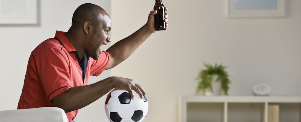 African man holding soccer ball and cheering