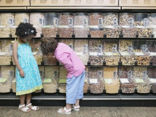 Children at a supermarket looking at assorted nuts stored in bulk food bins