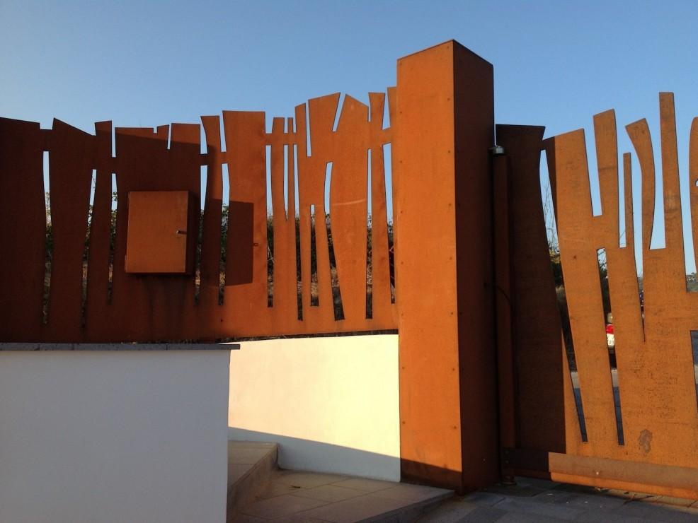 Tenuta di Castellaro, recinzione di ispirazione africana in acciaio cor-ten, di Luigi Radici