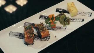Salmone croccante alle erbe e pistacchi con verdure e salsa al nero di seppia