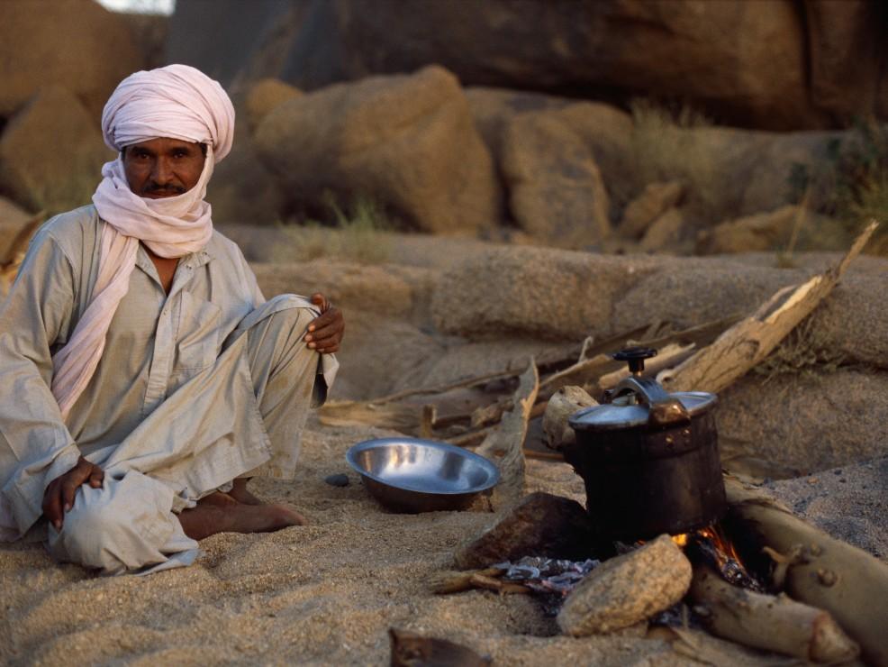 Algeria, La maggior parte della popolazione algerina è composta da una base etnica berbera. In questa foto, un uomo sta cucinando in un campo