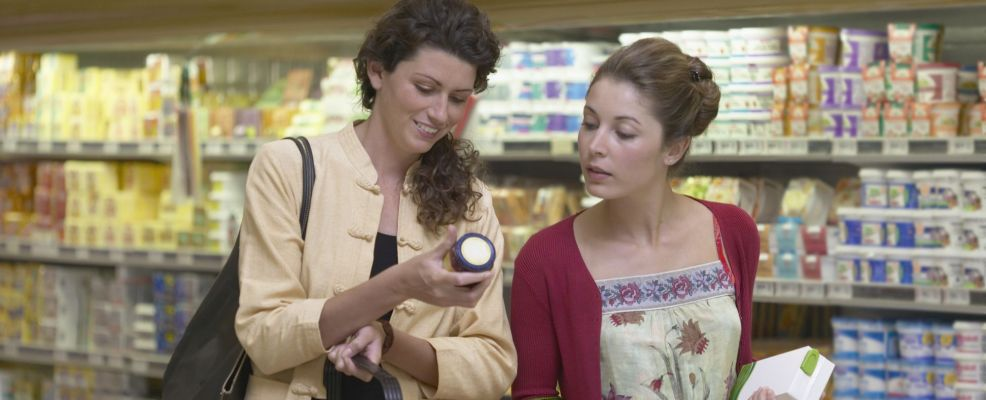 Two women waling through the dairy section of a supermarket