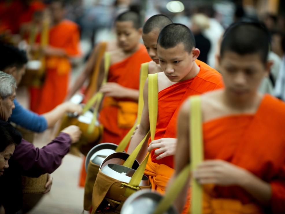 Durante la cerimonia del Tak Bat i monaci raccolgono il riso dai fedeli che li attendono inginocchiati lungo la strada