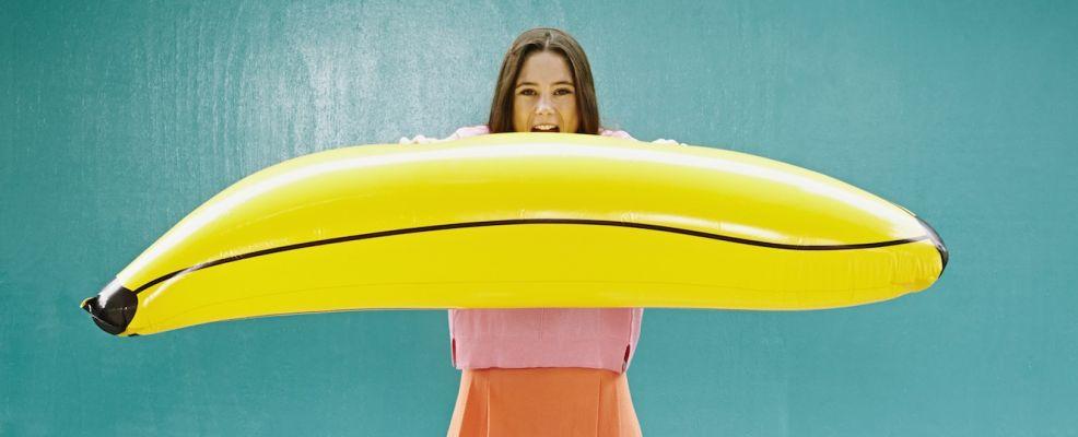 Young woman blowing inflatable banana