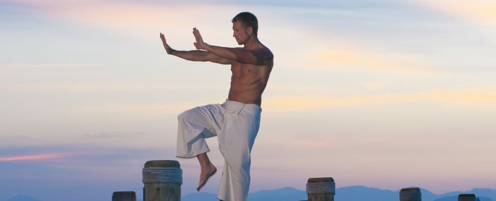 Fit Man Exercising with Yoga on Pier