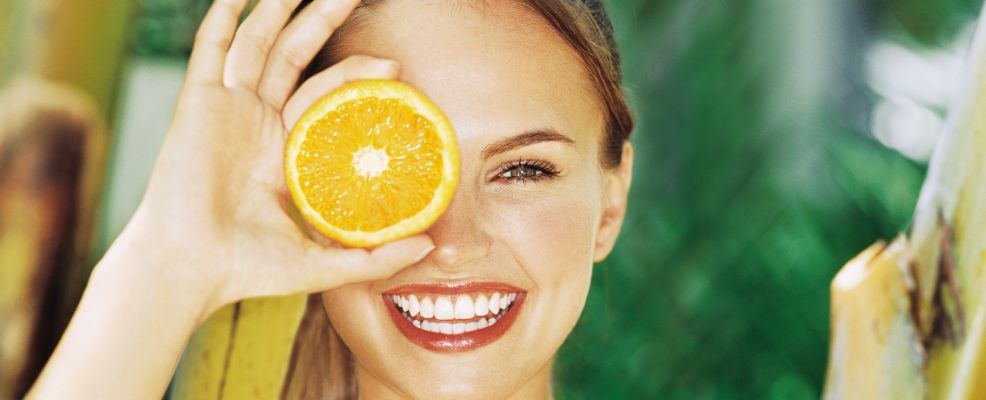Smiling young woman holding an orange