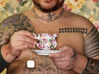 Heavily Tattooed Man Holding Floral Tea Cup