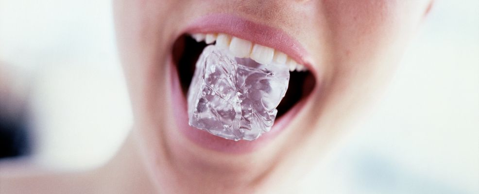 Young woman with ice cube in her mouth