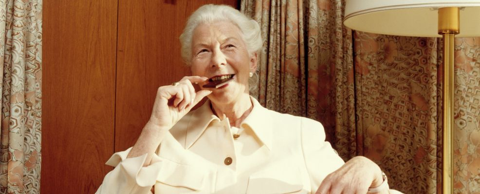 Female senior eating a chocolate biscuit