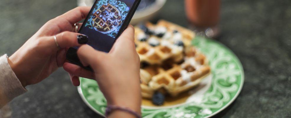 Hand using smartphone to take photo of breakfast