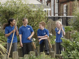 Group of four school children with gardening tools