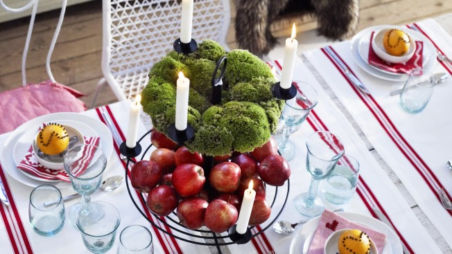 Close up of Christmas place setting with candles and fruits