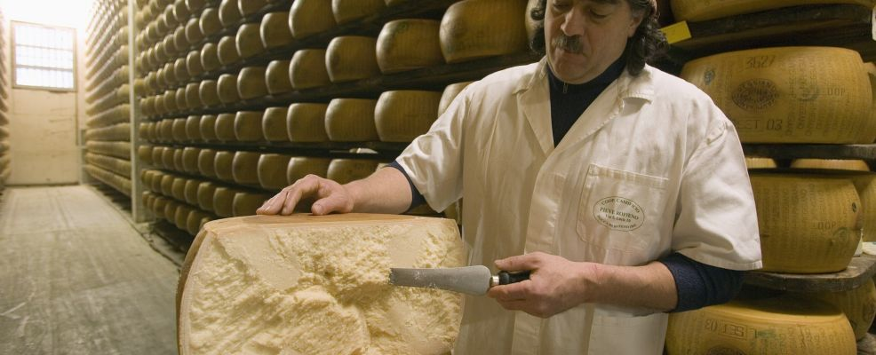 Man with Freshly Cut Wheel of Parmigiano-Reggiano Cheese