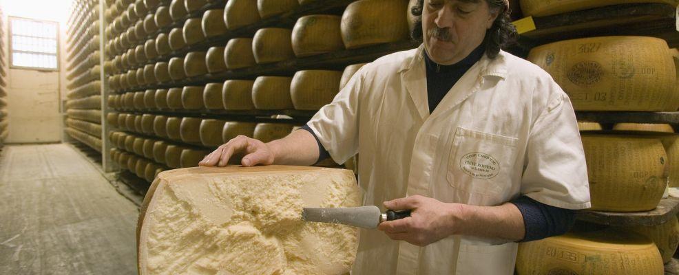 Man with Freshly Cut Wheel of Parmigiano-Reggiano Cheese