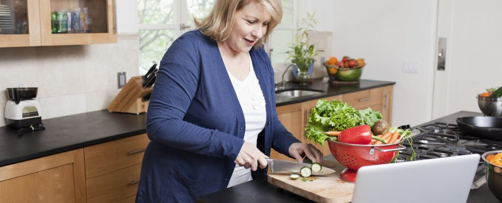 Woman chopping vegetables and using laptop in kitchen