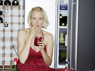 Woman eating on floor by fridge