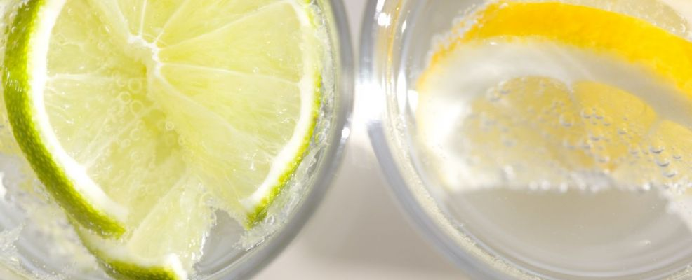 Extreme close up of two glasses of sparkling water with lemon and lime