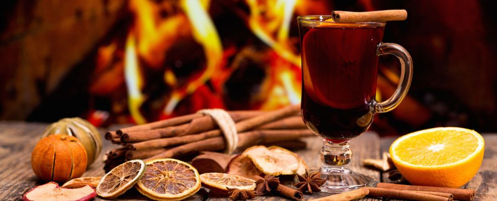 65328020 - glass of christmas mulled wine on wooden table against fireplace