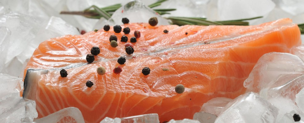 55972624 - salmon steak on ice cubes with rosemary and lemon. top view