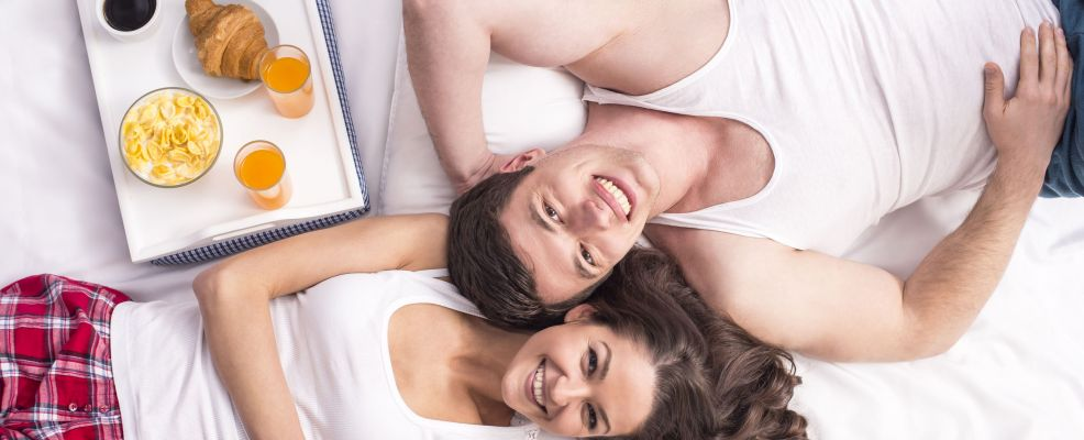38720525 - top view. smiling young couple having breakfast  in bed.